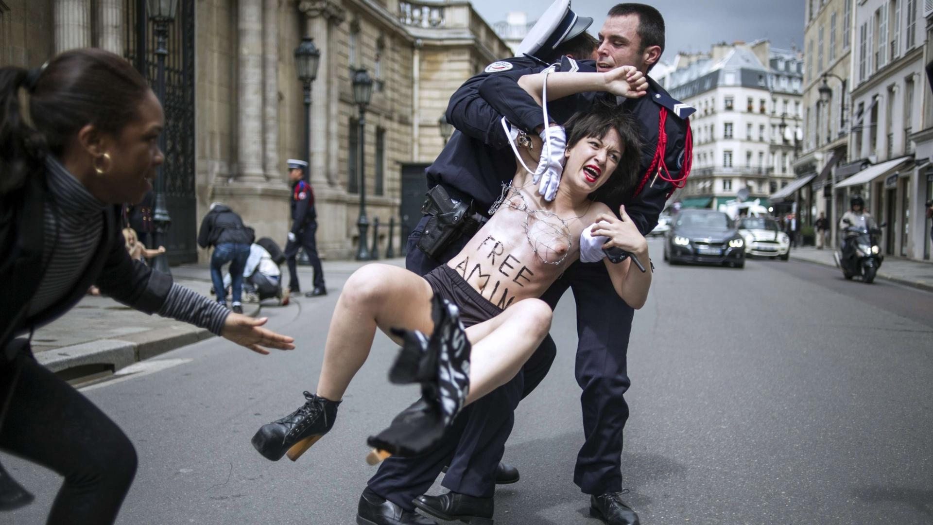 3.jul.2013 - Policial prende uma ativista do Femen que protestava do lado de fora do Palácio Elysee, em Paris, residência oficial do presidente da França, François Hollande, nesta quarta-feira (3). Com arame farpado ao redor dos seios, as mulheres exigigiam a libertação da ativista Amina Sboui, presa na Tunísia em maio por pichar o nome do grupo em uma parede na cidade de Kairouan. Hollande fará uma visita de dois dias, a partir de quinta-feira (4), para entregar uma mensagem de