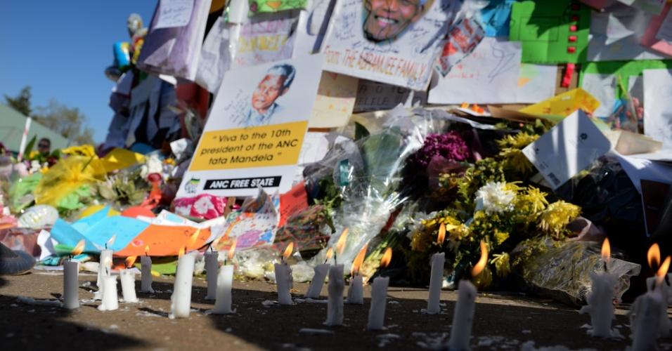 3.jul.2013 - Velas queimam em frente a uma parede de mensagens e flores deixadas em homenagem ao ex-presidente Nelson Mandela, que está internado no Hospital do Coração Mediclinic, em Pretória, África do Sul. Mandela, que completa 95 anos no próximo mês, foi levado às pressas para o hospital há três semanas com uma doença pulmonar