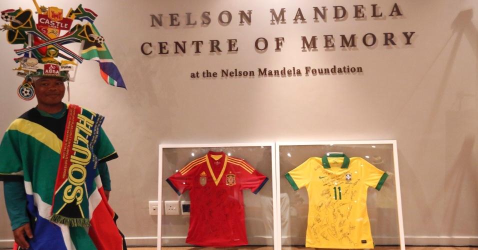 4.jul.2013 - Fã posa ao lado de camisetas autografadas das finalistas da Copa das Confederações (Espanha e Brasil). As seleções presentearam o Centro de Memória Nelson Mandela, em Joanesburgo, na África do Sul. O estado de saúde do ex-presidente sul-africano é grave, mas estável