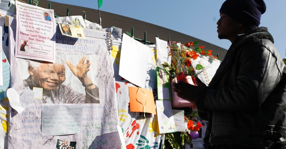 """4.jul.2013 - Homem reza em frente ao Hospital do Coração Mediclinic, onde o ex-presidente sul-africano está internado em Pretória. Segundo o governo, o estado de saúde de Mandela é """"crítico, mas estável"""""""