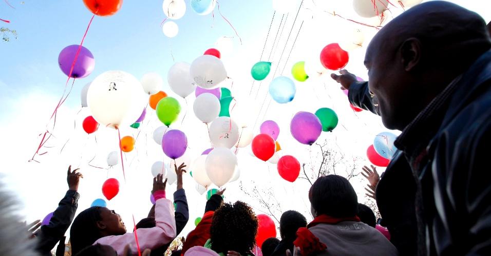 5.jul.2013 - Sul-africanos soltam balões diante do hospital em Pretória, onde Nelson Mandela é tratado de uma infecção pulmonar, na manhã desta sexta-feira (5)