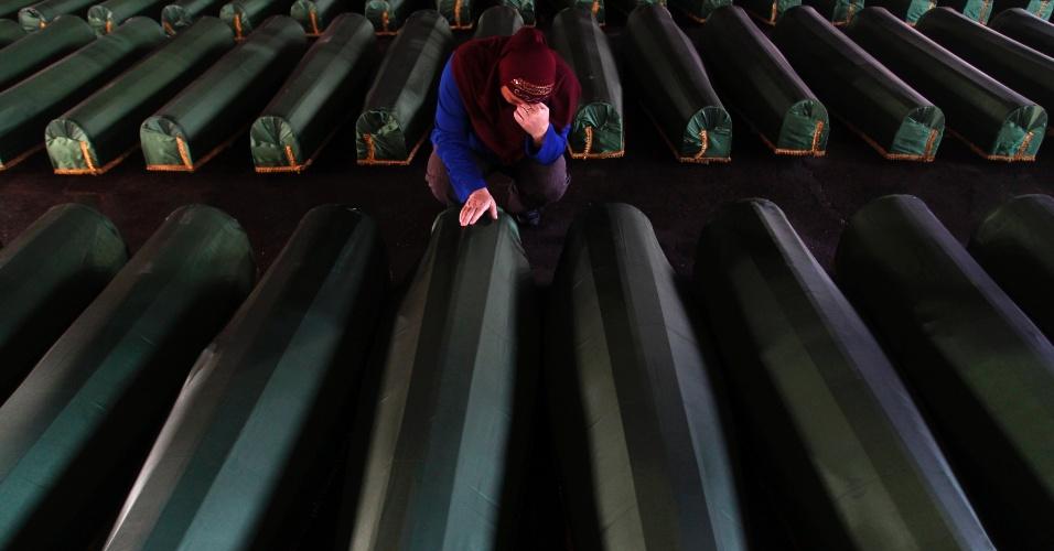 10.jul.2013 - Mulher bósnia chora ao lado do caixão de um parente, nesta quarta-feira (10), em Srebrenica, na Bósnia-Herzegóvina.  Cerca de 410 corpos foram recentemente identificados, vítimas do Massacre de Srebrenica em 1995, no qual forças sérvias comandadas por Ratko Mladic fizeram ao menos 8 mil vítimas muçulmanas e posteriormente os enterraram em covas coletivas