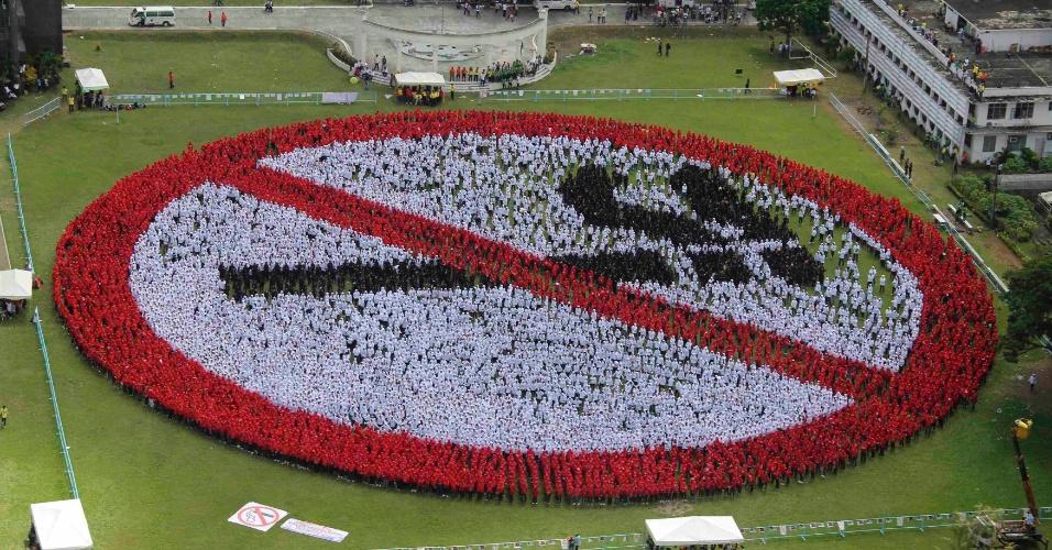 29.jun.2013 - Milhares de filipinos tentam formar o sinal de ?não fume? no campo de ma universidade ao sul de Manila. A tentativa é de criar a maior placa antitabagismo do mundo e conseguir uma marca no Guinness Book