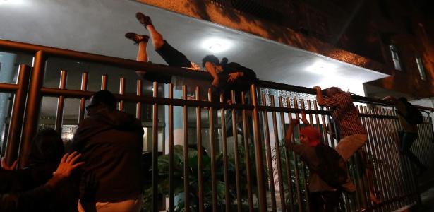 Manifestantes tentam escapar da polícia próximo ao Palácio da Guanabara, sede do governo do Rio de Janeiro, em protesto pela renúncia do governador