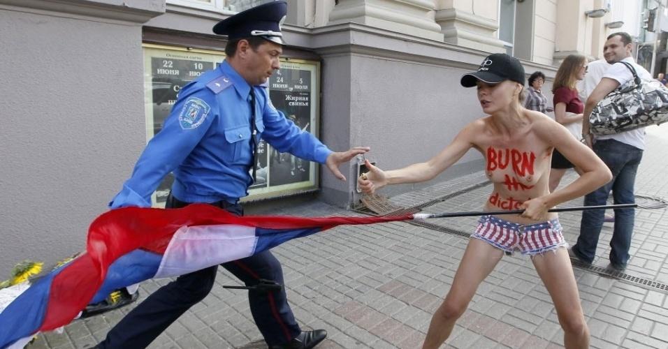 18.jul.2013 - Policiais ucranianos detêm ativista do grupo feminista Femen durante protesto em Kiev, na Ucrânia, a favor de Alexei Navalny, um dos maiores opositores do presidente russo Vladmir Putin, que foi considerado nesta quinta-feira (18) culpado de roubo e fraude e sentenciado a cinco anos de prisão pelo tribunal de Kirov, na Rússia. Navalny, que ajudou a organizar em 2011 uma das maiores manifestações contra o governo russo, diz que o julgamento teve motivações políticas