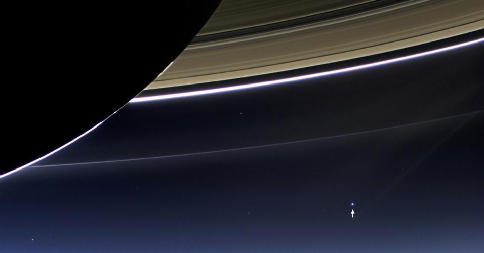 """22.jul.2013 - A Nasa (Agência Espacial Norte-Americana) divulgou nesta segunda-feira (22) a imagem tratada e colorida do registro simultâneo da Terra e de Saturno feita pela sonda Cassini no dia 19 de julho. Das 33 imagens do sistema de anéis, apenas esta mostra os dois planetas ao mesmo tempo: a Terra surge como um """"pálido ponto azul"""" no canto direito (indicada pela seta), enquanto três anéis (F, G e E) são iluminados por trás pelo Sol, enaltecendo ainda mais o lado escuro de Saturno"""