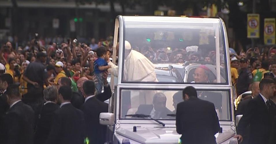 22.jul.2013 - O papa Francisco beija criança enquanto circula a bordo do papamóvel pelas ruas do centro do Rio nesta segunda-feira (22)