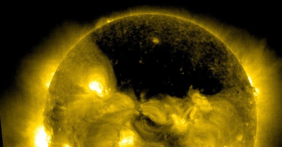 22.jul.2013 - Um buraco coronal gigantesco sobre a região do polo Norte do Sol foi captado pelo Observatório Solar Heliosférico (SOHO, na sigla em inglês) no dia 18 de julho, às 09h06 EDT (às 10h06, no fuso de Brasília). Os buracos coronais são, na verdade, regiões escuras e de baixa densidade que surgem na atmosfera mais externa do Sol, a corona: como há pouco material solar e temperatura mais baixa do que a da vizinhança, eles parecem ser bem mais escuros do que o ambiente ao seu redor, explica a Nasa (Agência Espacial Norte-Americana)