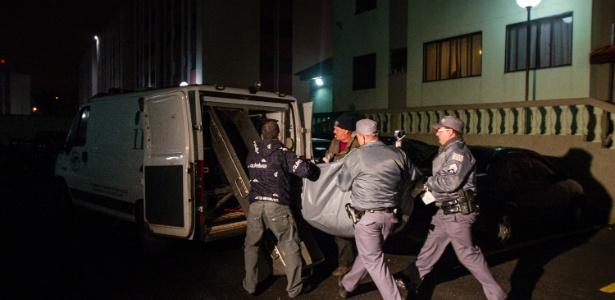 Agentes transportam corpo de mulher que, segundo a polícia, foi morta pelo filho e guardada em uma geladeira do apartamento onde moravam, na zona leste de SP