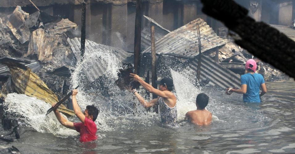24.jul.2013 - Filipinos tentam extinguir as chamas de um incêndio que atingiu uma favela, nesta quarta-feira (24), em  Pasay, norte de Manila. Cerca de 200 casas foram consumidas pelas chamas, e mais de 400 pessoas estão desabrigadas