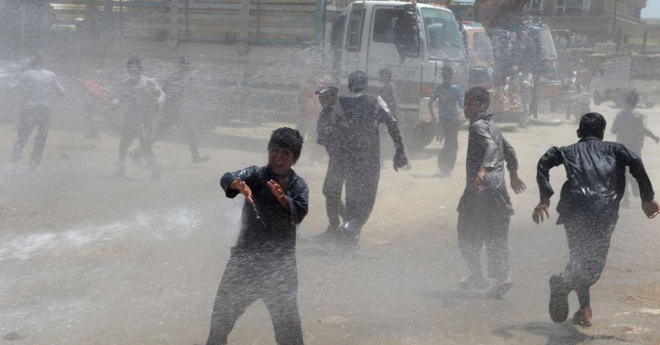 24.jul.2013 - Garotos afegãos se refrescam com jato de água espirrado por caminhão da prefeitura de Cabul, na manhã desta quarta-feira (24)