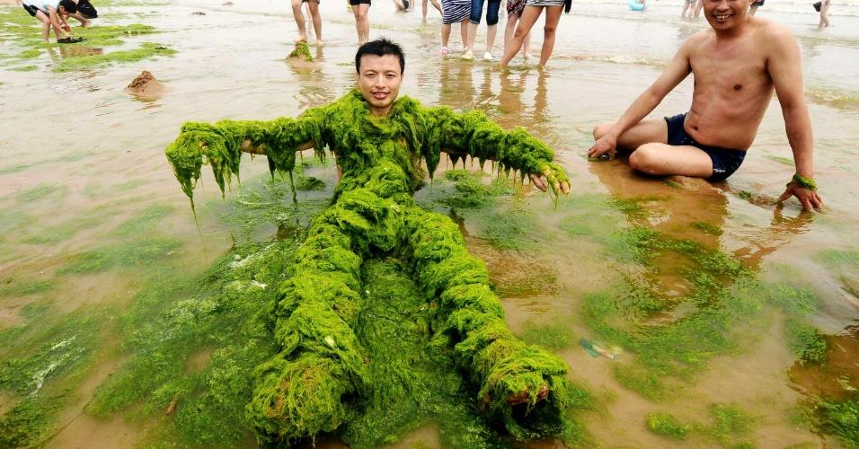 24.jul.2013 - Homem se cobre com algas e posa em praia de Qingdao, no leste da China