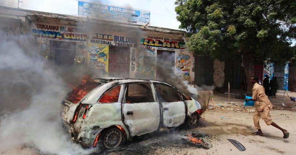 24.jul.2013 - Homem tenta apagar fogo em carro chamas depois que ele explodiu próximo do mercado de Hamaerweyne, em Mogadício (Somália)