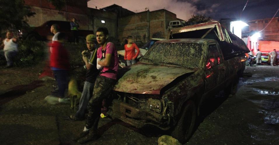 24.jul.2013 - Moradores se apoiam em carro coberto de lama depois que chuvas causaram deslizamentos de terra em Tegucigalpa (Honduras). Ao menos 14 casas foram soterradas, sem causar vítimas fatais