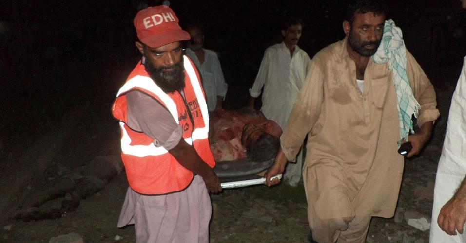 24.jul.2013 - Paquistaneses carregam o corpo de uma vítima da explosão de um carro-bomba, no sul da cidade de Sukkur, no Paquistão, nesta quarta-feira (24). Cerca de sete pessoas morreram, segundo autoridades locais, após o ataque de homens armados e carros-bomba a escritórios governamentais