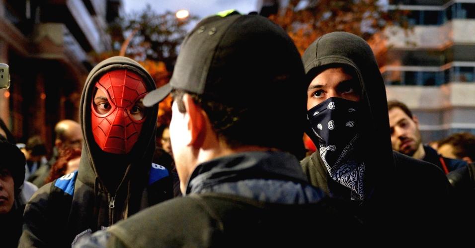 25.jul.2013 - Manifestantes mascarados ouvem recomendações de policial militar durante protesto nos arredores da residência do governador do Rio de Janeiro, Sérgio Cabral, nesta quinta-feira (25). Até uma máscara do Homem Aranha foi usada por um dos integrantes do grupo
