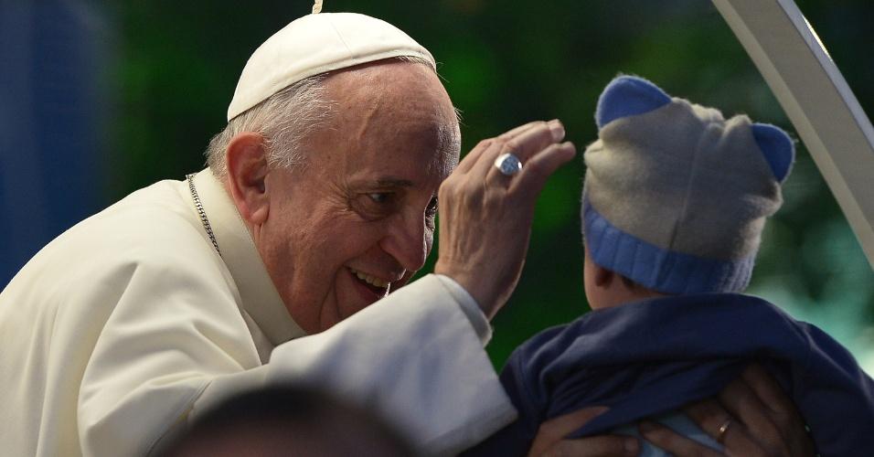 26.jul.2013 - Papa Francisco abençoa criança do papamóvel em rua de Copacabana. O pontífice segue rumo ao palco localizado no bairro, onde haverá a encenação da Via Sacra