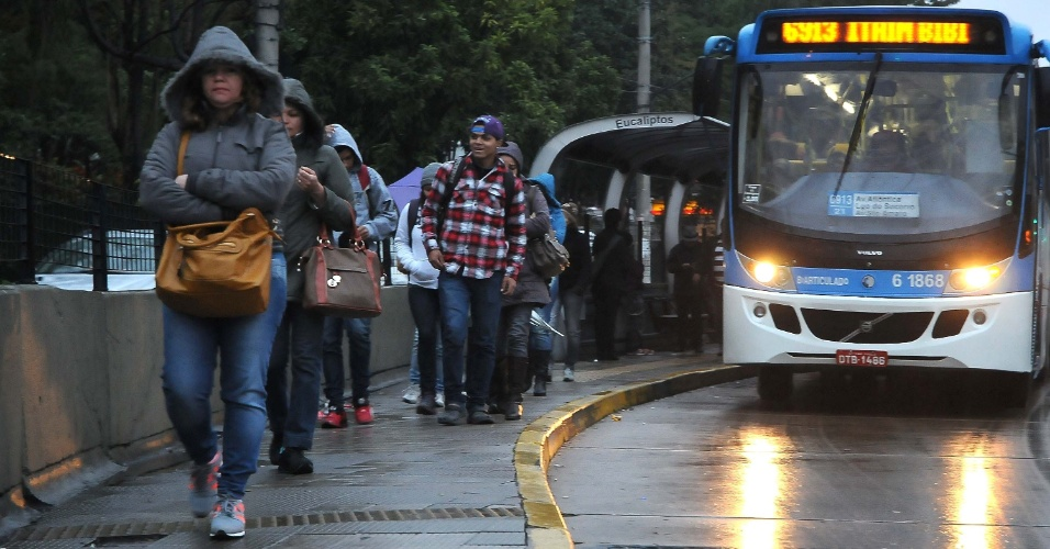 26.jul.2013 - Pedestres enfrentam manhã fria e chuvosa à espera de ônibus na avenida Santo Amaro, na zona sul de São Paulo