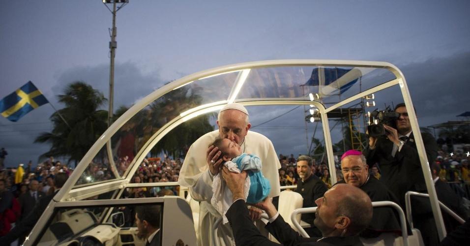 27.jul.2013 - Em foto divulgada neste sábado pelo Osservatore Romano, papa Francisco beija criança no papamóvel durante chegada à praia de Copacabana, no Rio de Janeiro, para assistir a encenação da via Crucis, na sexta-feira (26), durante a JMJ (Jornada Mundial da Juventude)