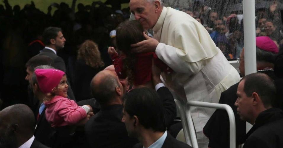 27.jul.2013 - Papa Francisco beija criança a caminho da Catedral Metropolitana do Rio de Janeiro onde celebra missa da JMJ (Jornada Mundial da Juventude)