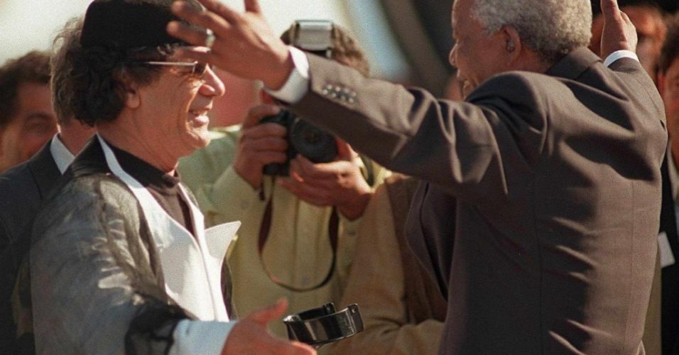 1999 - O já ex-presidente da África do Sul, Nelson Mandela, se prepara para abraçar seu colega da Líbia, Muammar Gaddafi, na chegada deste à Cidade do Cabo