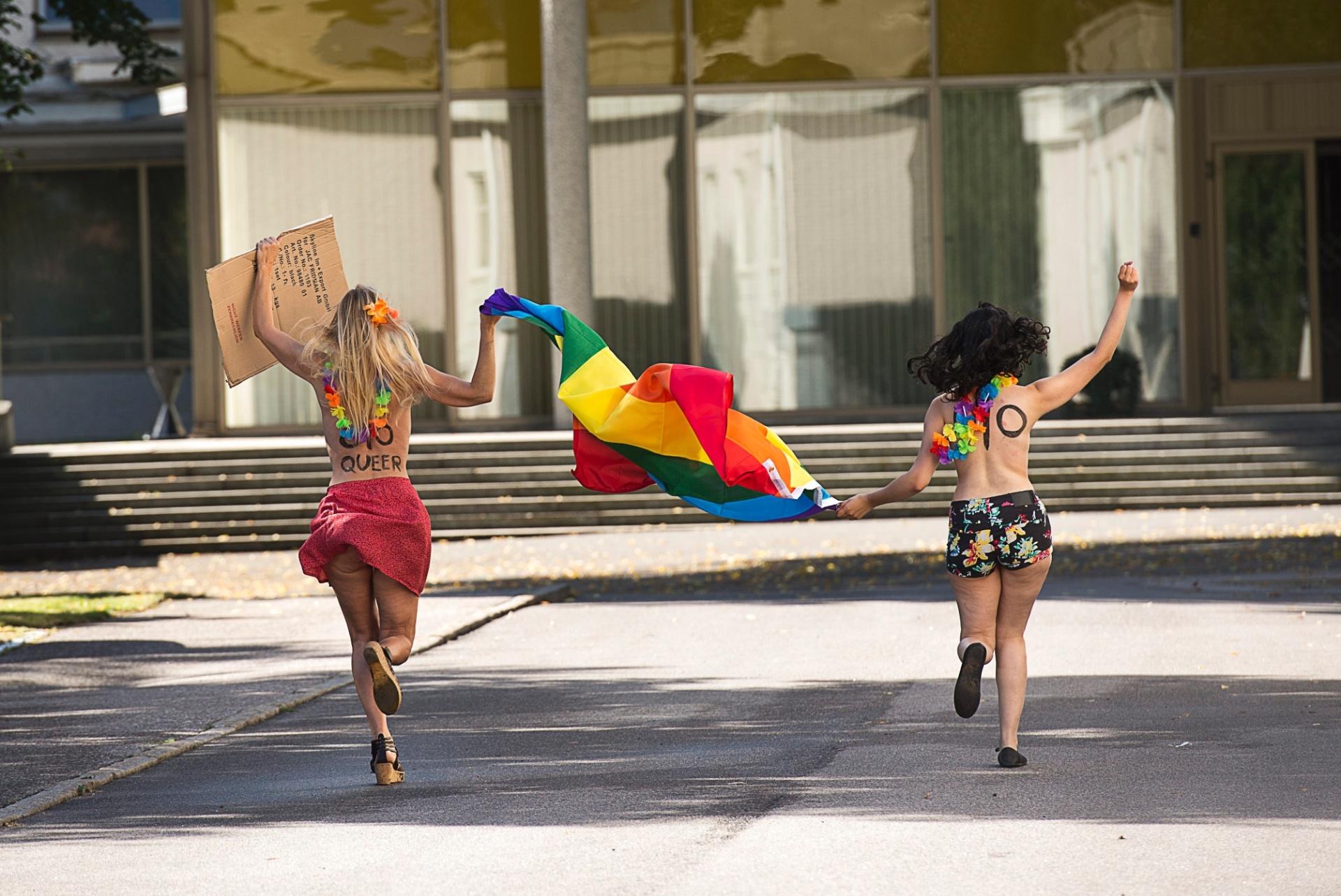 1º.ago.2013 - Ativistas do Femen (grupo feminista famoso pelos protestos com o uso de topless) correm segurando bandeira do arco-íris, símbolo do orgulho gay, em protesto em Estocolmo, na Suécia, nesta quinta-feira (1º). As ativistas protestam contra um projeto de lei antigay na Rússia e a estigmatização dos homossexuais