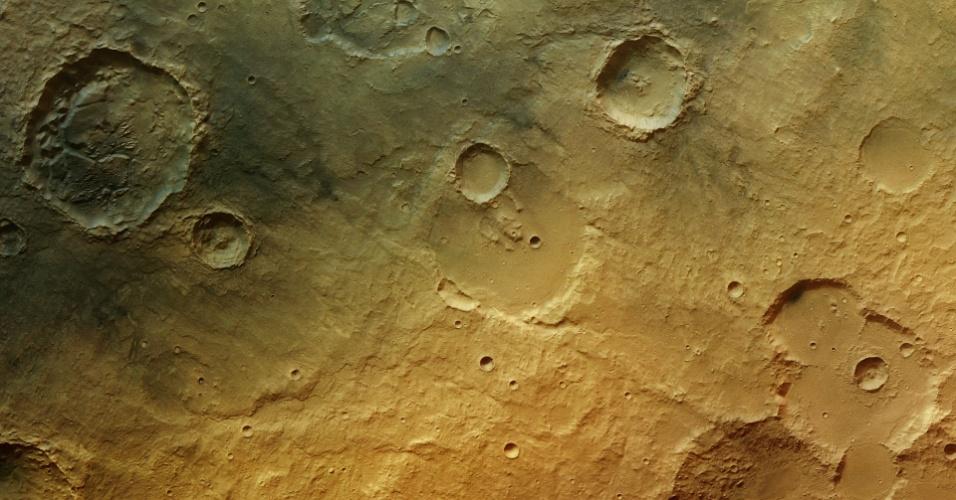 """1.ago.2013 - Uma cratera ao Sul do equador de Marte traz novas evidências que o planeta vermelho já teve água líquida em sua superfície, divulgou nesta quinta-feira (1º) a Agência Espacial Europeia (ESA, na sigla em inglês). Com 34 quilômetros de diâmetro, a cratera tem vários blocos de pedra (no topo, à esquerda) que se formaram com a sedimentação de partículas dissolvidas em água depois de uma inundação, criando uma forma """"caótica"""", mostram fotos da sonda Mars Express, que orbita Marte desde 2003. Outros traços do passado molhado do planeta são vistos na forma de canais (centro) e de um curso sinuoso entre duas deformações (no topo, à direita)"""