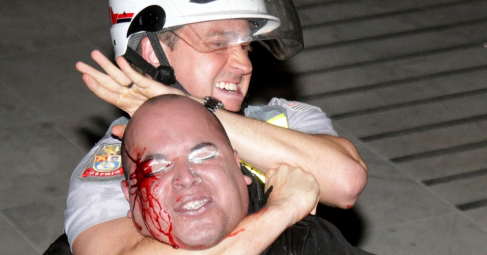 2.jul.2013 - Policial militar imobiliza manifestante ferido durante protesto contra os governos de São Paulo e Rio, em frente à Alesp (Assembleia Legislativa de São Paulo), na noite desta sexta-feira (2)