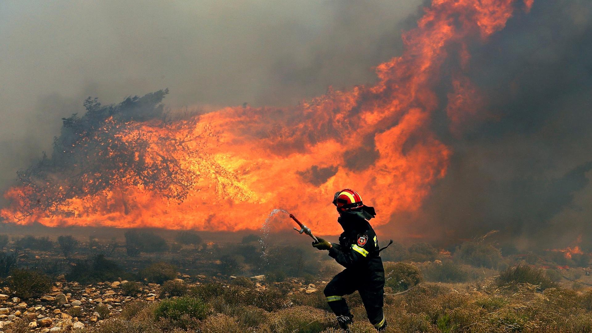 5.ago.2013 - Bombeiro corre com mangueira para apagar um incêndio florestal que atinge Maratona, perto de Atenas, na Grécia. O incêndio, espalhado por fortes ventos, se alastrou atingindo diversas casas