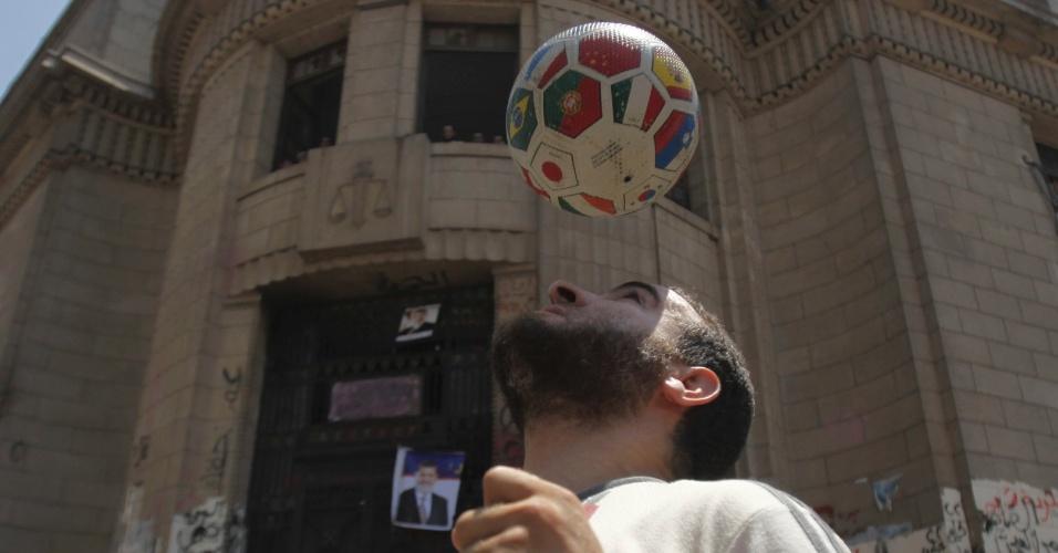 5.ago.2013 - Membro da irmandade muçulmana e apoiador do presidente egípcio deposto, Mohamed Mursi, joga bola de futebol durante protesto no Cairo, nesta segunda-feira (5)