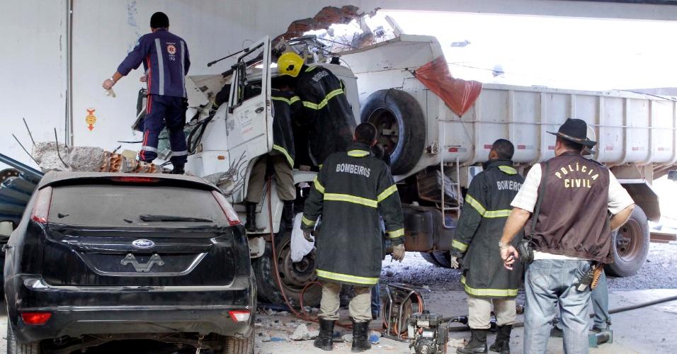 5.ago.2013 - O motorista de um caminhão caçamba perdeu o freio do veículo e bateu no muro de uma oficina de funilaria em Cuiabá (MT), nesta segunda-feira (5). Ele atravessou a pista e derrubou três postes antes de se chocar com o muro. Uma mulher de 49 anos que dirigia uma moto foi atingida por fios de energia e morreu no local. O motorista ficou preso nas ferragens, foi socorrido e internado em um hospital da região