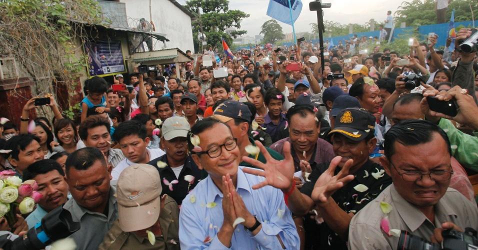 5.ago.2013 - Presidente do partido oposicionista do Camboja Cnpr, Sam Rainsy (centro) saúda apoiadores durante visita ao lago Boeung Kak, em Phnom Pehn. Ele convocou um protesto em massa contra o governo para esta terça-feira (6), após supostas irregularidades nas eleições