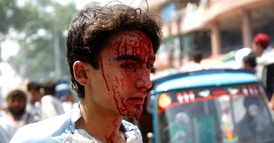 6.ago.2013 - Garoto ferido com sangue no rosto caminha de local de explosão a bomba na província de Jalalabad (Afeganistão), nesta terça-feira (6). Uma bomba controlada remotamente explodiu, matando uma pessoa e deixando três feridos