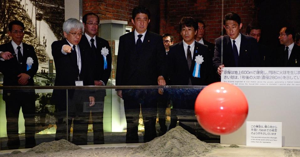 6.ago.2013 - O primeiro-ministro japonês, Shinzo Abe (centro) ouve explicação sobre o bombardeio atômico de 1945 de Kenji Shiga (segundo à esquerda), diretor do Memorial da Paz, em Hiroshima, nesta terça-feira (6). Cerimônias são realizadas para marcar o 68º aniversário do bombardeio atômico dos Estados Unidos à cidade japonesa. Dezenas de milhares de pessoas, incluindo sobreviventes idosos, parentes, funcionários do governo e delegados estrangeiros fizeram um minuto de silêncio às 8h15 local, momento da detonação, que transformou a cidade em um inferno nuclear em 1945