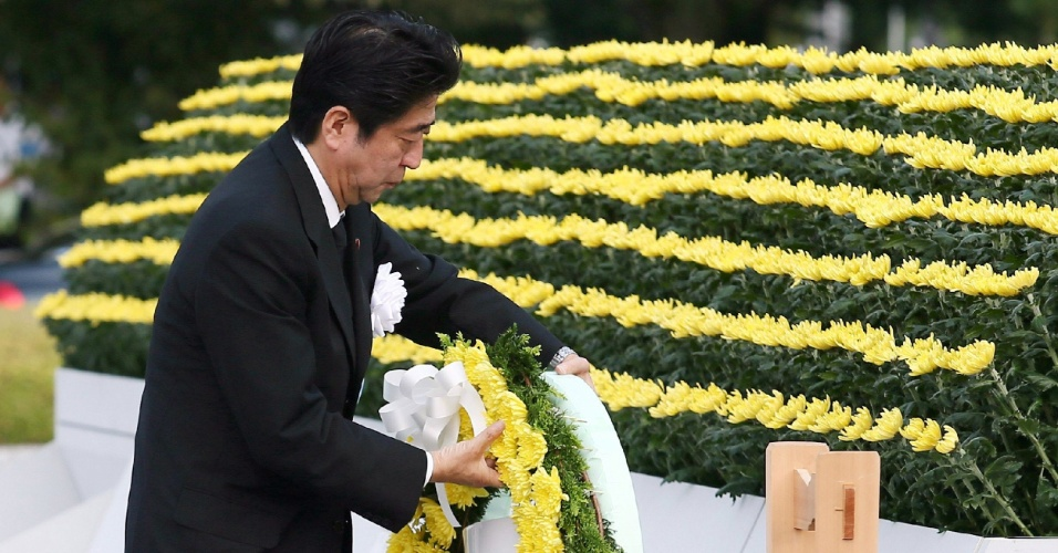 6.ago.2013 - O primeiro-ministro japonês Shinzo Abe deposita uma coroa de flores sobre o altar da bomba atômica, no parque Memorial da Paz, em Hiroshima, na manhã desta terça-feira (6), data que marca, às 8h15 no horário local, os 68 anos da explosão nuclear que destruiu a cidade durante a 2ª Guerra Mundial. Até hoje o Japão é o único país atingido por bombas nucleares com fins bélicos