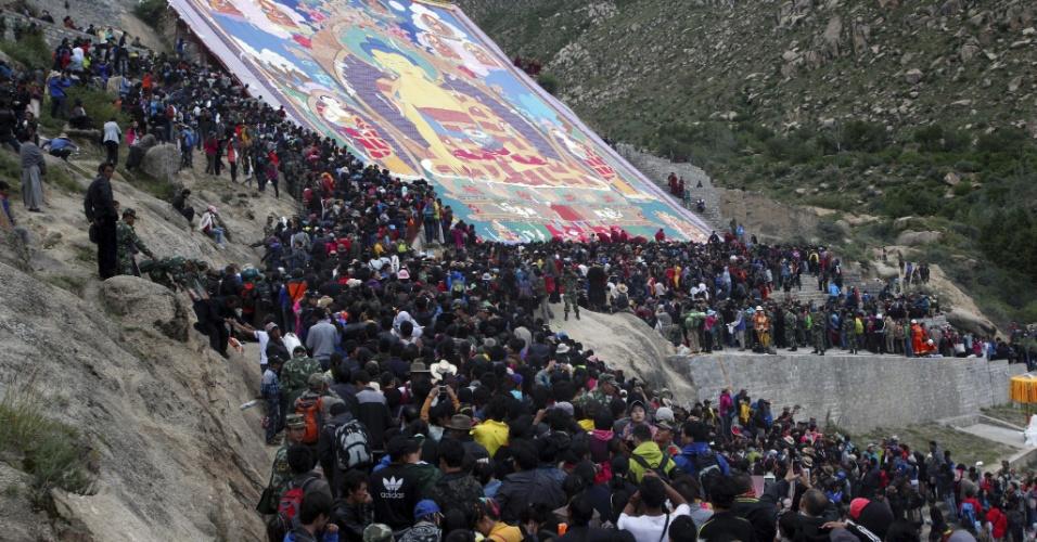 6.ago.2013 - Turistas e peregrinos se reúnem junto a imagem gigante de Buda no monastério Drepu, Lhasa, no Tibete (atualmente pertencente à China), nesta terça-feira (6). De 6 a 12 de agosto se celebra o festival de Sho Dun, em que se descobre uma imagem gigante da figura máxima do budismo