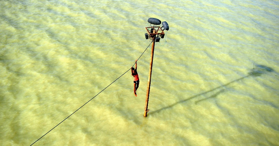 6.ago.2013 - Um jovem indiano se pendura em um fio da rede de energia antes de pular nas águas transbordadas do Rio Ganges, em Allahabad, na Índia, nesta terça-feira (6). O país convive com as monções que atingem o continente entre junho e setembro. Elas correspondem a corresponde a 80% das precipitações anuais da Índia e provocam enchentes