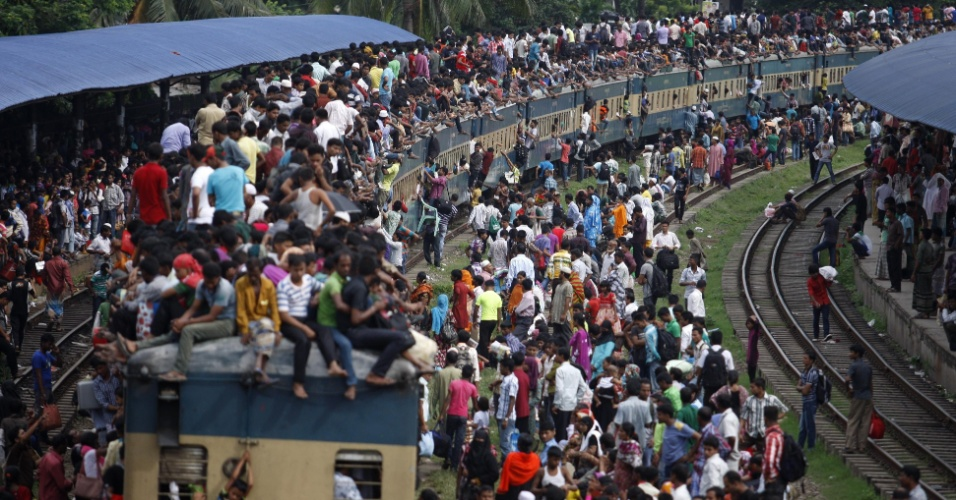 8.ago.2013 - Centenas de muçulmanos se arriscam viajando em cima de trem lotado, em Dacca (Bangladesh)