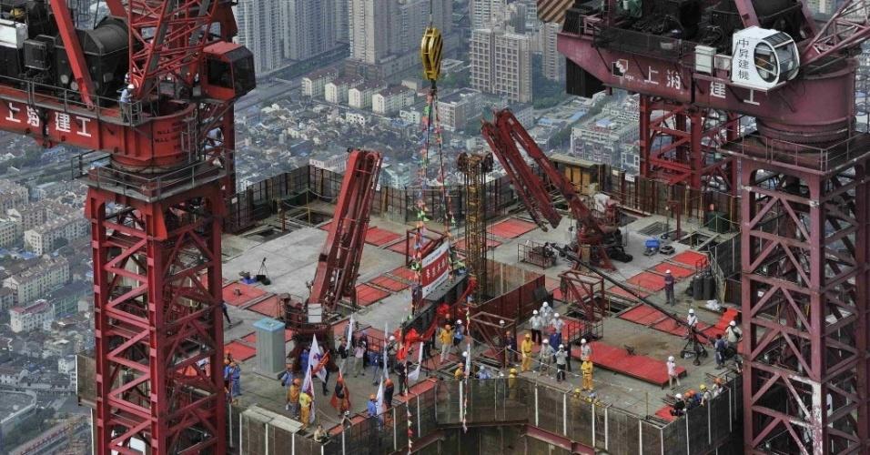 8.ago.2013 - Guindaste ergue a última peça de aço do topo da Torre Xangai, que está em construção no distrito financeiro de Pudong, em Xangai. A torre de 632 metros deve se tornar o edifício mais alto da China e o segundo mais alto do mundo