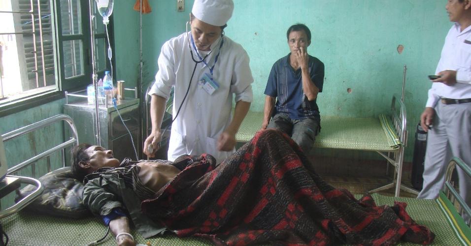 8.ago.2013 - Médico examina Ho Van Thanh (deitado), 82, depois de ser encontrado em floresta na província de Quang Ngai, no Vietnã