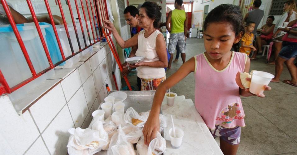 8.ago.2013 - Moradores afetados por incêndio na comunidade do Campinho, no bairro dos Coelhos, em Recife, tomam café da manhã em uma escola. Famílias desabrigadas ainda estão dormindo na escola, onde também recebem doações de água, comida e roupas