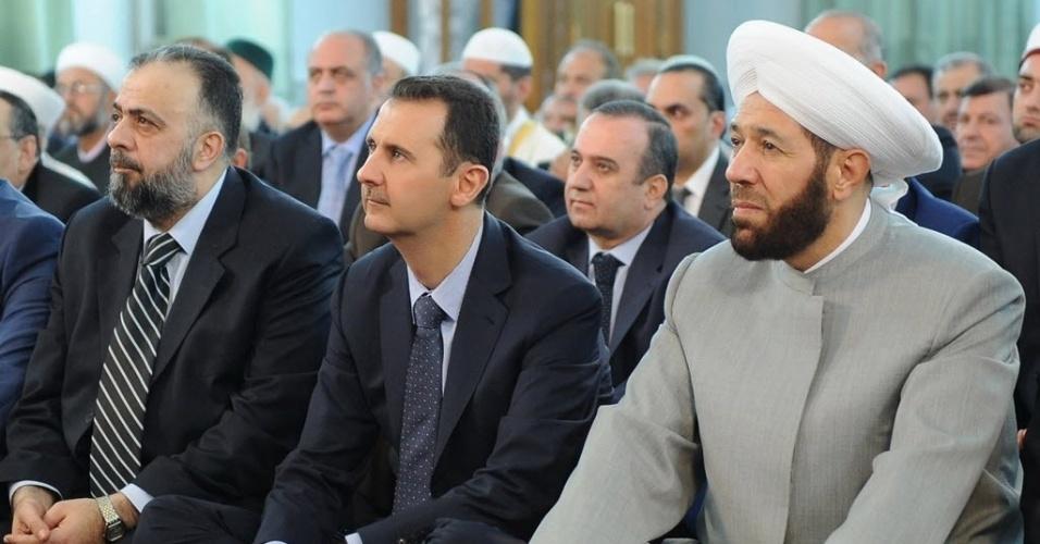 """8.ago.2013 - O presidente sírio, Bashar Assad (o 3º, da esq. para a dir.), participa da celebração do Eid al-Fitr, que marca o fim do mês sagrado dos muçulmanos, o Ramadã, nesta quinta-feira (8), na mesquita de los Omeyas, em Damasco. A imagem, divulgada pela agênica de notícias síria SANA, contradiz a informação veiculada hoje pela TV """"Al Arabia"""" de que Assad teria sido alvo de um ataque que atingiu o comboio presidencial. O Exército negou o incidente. Segundo o OSDH (Observatório Sírio de Direitos Humanos), houve um ataque a bomba nas imediações da mesquita, mas o bombardeio, que não deixou vítimas nem danos materiais, não teve Assad como alvo"""