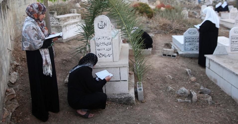 8.ago.2013 - Palestinas rezam perto de túmulos em cemitério em Deir al Hatab (perto de Nablus) primeiro dia de celebração do Eid al-Fitr, que marca o fim do mês sagrado do Ramadã