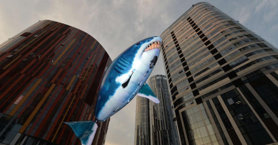 8.ago.2013 - Um tubarão inflável flutua entre prédios de Pequim durante uma campanha do Instituto Jane Goodall. O objetivo é tentar convencer os chineses a não consumir sopa de barbatana de tubarão, que é uma iguaria local