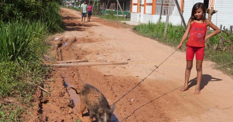11.ago.2013 - A menina Nalanda Costa, 9, passeia com porco de estimação na cidade de Melgaço (a cerca de 300 km de Belém)