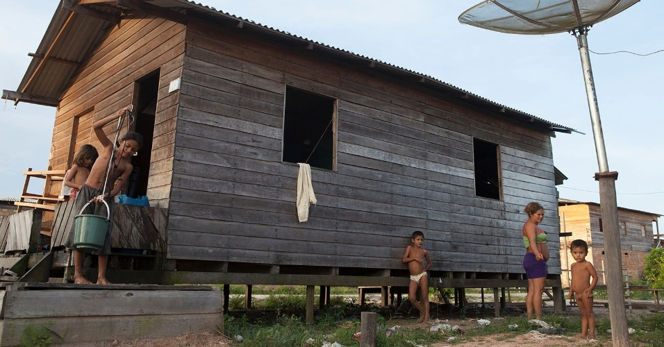 11.ago.2013 - Crianças ajudam as mães nas tarefas domésticas em casas de palafitas, construídas centímetros acima do solo para evitar inundação na época das cheias
