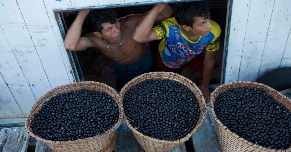 11.ago.2013 - Eliel Soares (à esquerda) e seu sócio vivem da exploração do açaí, principal fonte de renda e base da alimentação dos moradores locais. Cada balde é vendido por R$ 5, em média. O produto é levado até comunidades ribeirinhas mais distantes