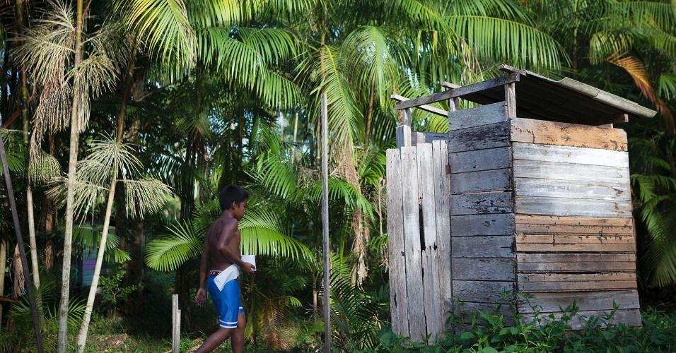 11.ago.2013 - Garoto caminha com papel-higiênico nas mãos em direção a um banheiro com fossa. Sem esgoto encanado, instalação é a melhor solução para algumas famílias
