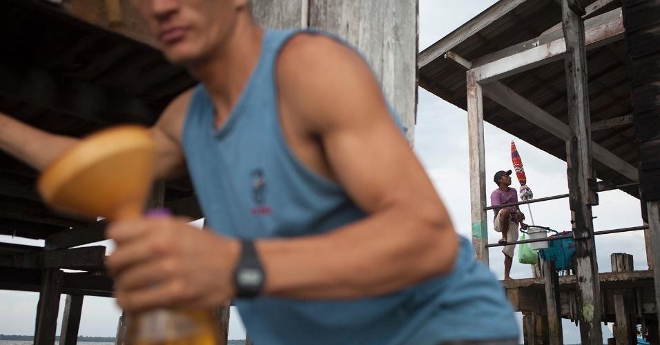 11.ago.2013 - Homem compra gasolina em posto oficial da cidade, improvisado em palafita no trapiche central, enquanto o sorveteiro espera o inconstante turismo da região