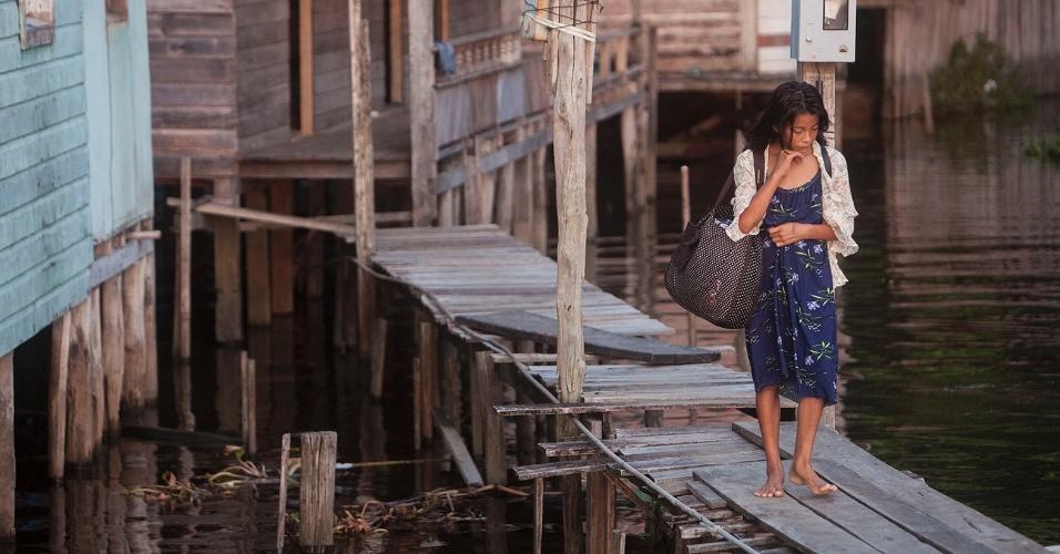 11.ago.2013 - Mulher caminha por pasarela de madeira que leva a palafitas na região de Melgaço. Acesso ao local é feito somente por via fluvial